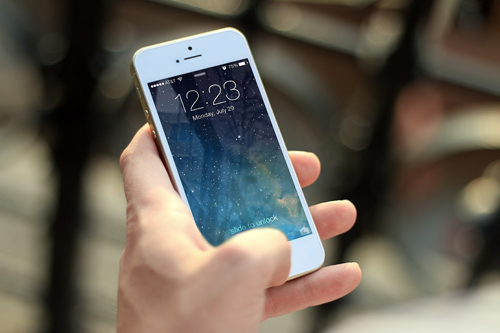 Hand holding an iPhone at its lock screen against a blurred fence background.