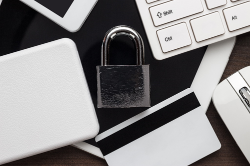 A padlock amongst various electronics, representing what two-factor authentication is.