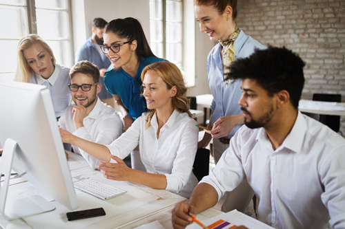 Productive, happy employees gather around a computer desk. Find out ways to increase employee productivity.