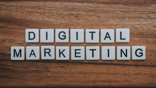 """""""Digital Marketing"""" spelled out using tiles on a wooden surface. Online marketing methods help reach your customers."""