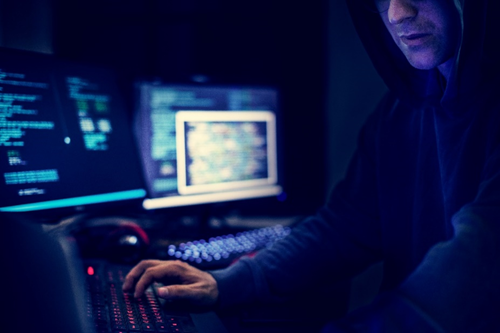 Hacker sits in a dark room at his computer, posing a cybersecurity threat to organizations in 2020
