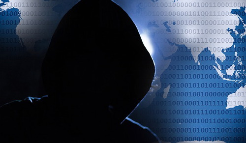 A hooded hacker stands against a background of the world with binary code. Targeted attacks from hackers like this are leading cybersecurity incidents.
