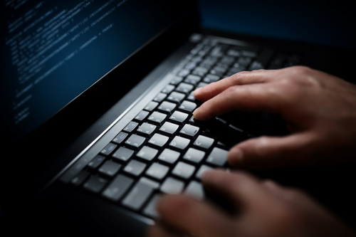 Hands type on laptop keyboard. Hackers Are Targeting Remote Workers like this.