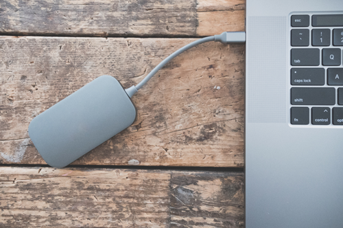 A hard drive plugged into a MacBook, demonstrating the importance of data backup.