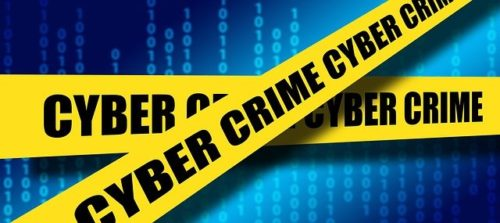 Yellow barricade tape with 'Cyber Crime' written on it against a blue coding background. There are many expected coronavirus cyberthreats in 2021.