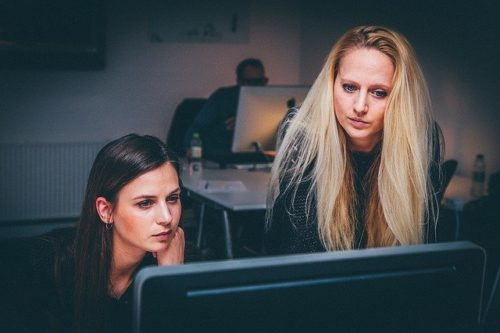 A woman helps another woman at her computer. These women must pick the best choice for themselves from in-house IT vs MSP.