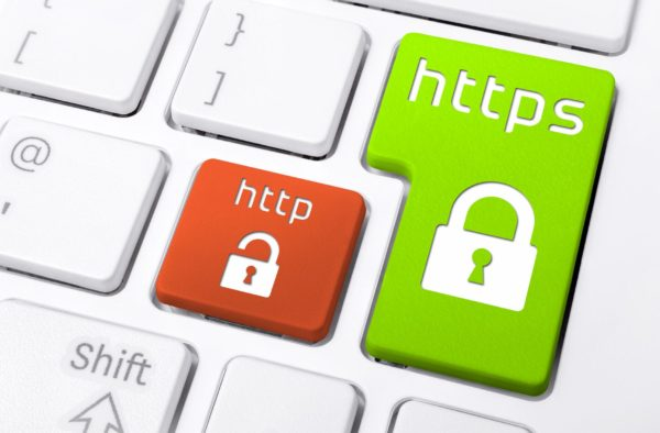 Keyboard closeup with green HTTPS locked padlock beside red HTTP unlocked padlock buttons.
