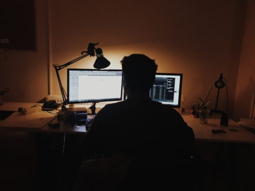A man sits in front of two monitors.