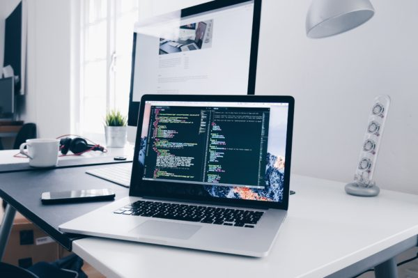 A Macbook with lines of code on a busy desk. Use these Mac security tips to protect your devices.