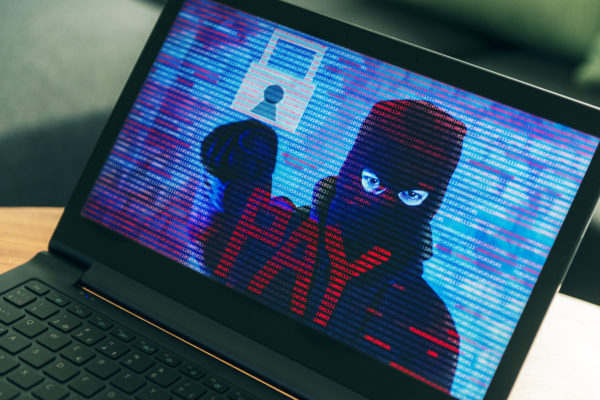 Criminal hiding behind a mask turns up on computer screen asking the owner for money. Concept of phishing and ransomware, where the computer has all files on the hard drive encrypted and the victims need to pay a ransom in order to get their files unlocked.