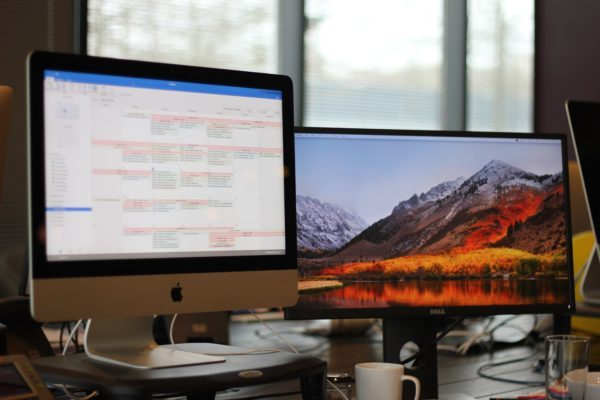 Turned-on iMac monitor and Dell monitor set-up as dual monitors on busy work desk.