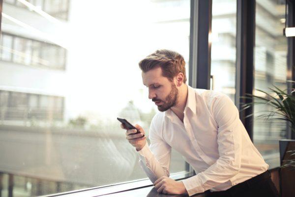 A businessman texting near window.
