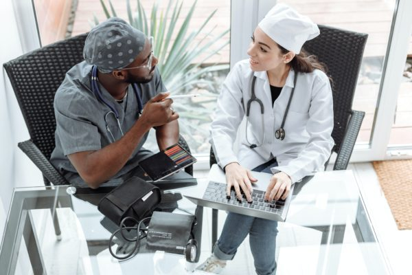 Two medical personnel sitting beside each other working on a laptop. Your healthcare practice needs managed IT services to stay safe.