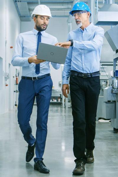 Two men walking and holding laptop.