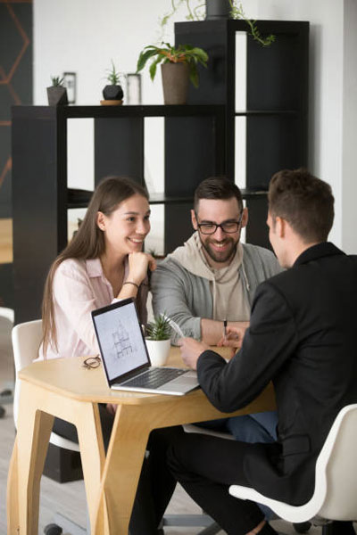 Realtor with laptop talking to couple.
