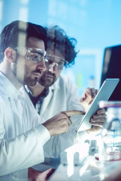 Scientists working on tablet in lab.