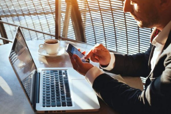 Business man using Wi-Fi on phone and laptop at café. These business Wi-Fi mistakes could be costing you.